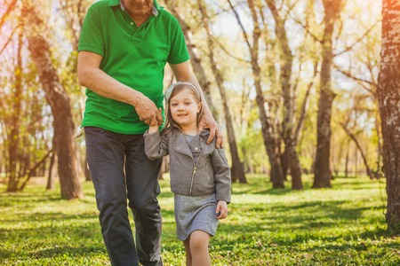 anonymous people: Lovely girl walking with grandfather in park Stock Photo