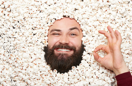 Man gesturing while lying in popcorn