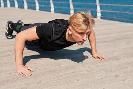 Fit man pushing up on pier