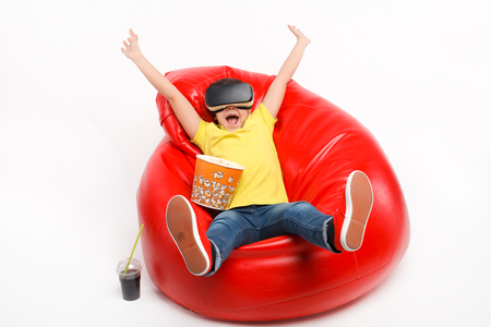 simulator: Cheerful kid in VR headset in armchair