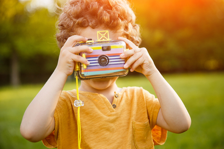 Youngster taking picture on green meadow