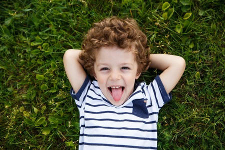 Curly-haired boy lying on grass Stock Photo