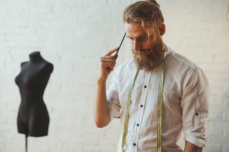 considering: Handsome designer looking pensive in atelier Stock Photo