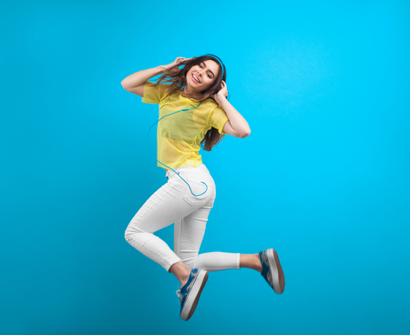 Teenage girl in headphones jumping