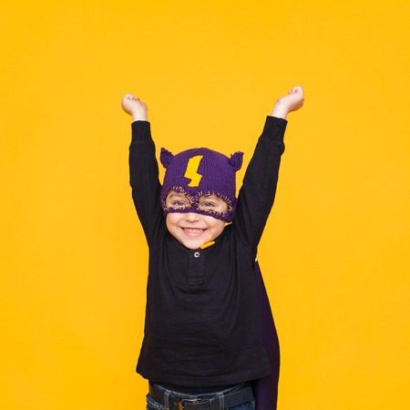 Cheerful kid in superhero costume