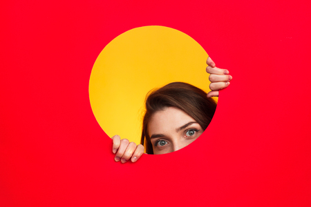 Woman looking out of circle in cardboard