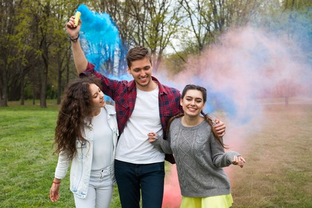 Young friends firing colourful smoke torches Stock Photo