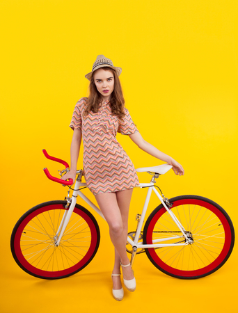 Confident model leaning on bicycle