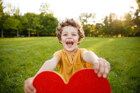 Smiling boy holding heart in park Stock Photo