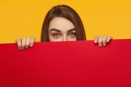 urprised woman hiding behind sheet of red cardboard Stock Photo