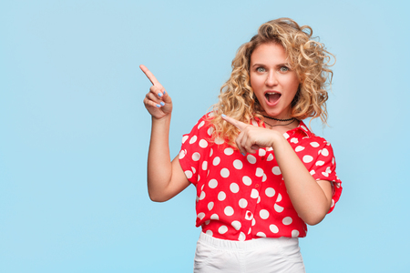 Blonde woman in red shirt making gesticulation