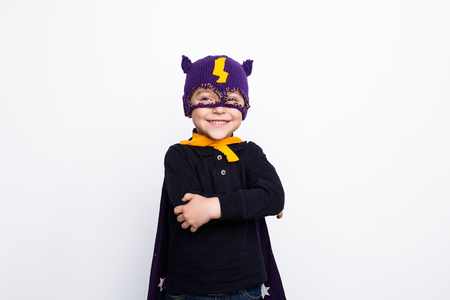 Adorable kid in knitted superhero hat Imagens