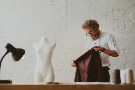 Tailor looking at piece of fabric