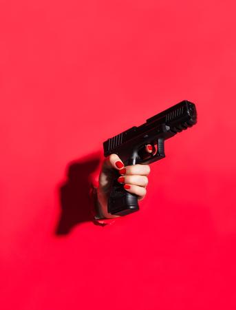 Crop female hand with gun