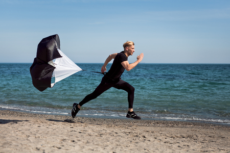 Man running with parachute on beach