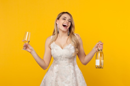 Happy girl laughing holding wine bottle Фото со стока