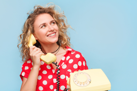 Smiling woman holding receiver Stock Photo