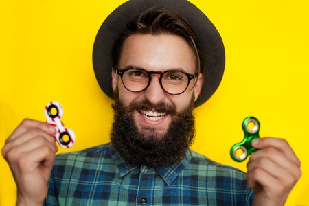 Happy smiling hipster man with fidget spinners