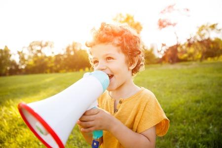 Boy standing in field speaking in megaphone