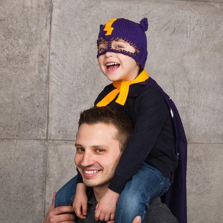pretending: Boy in hero costume on fathers shoulders Stock Photo
