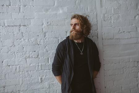 Bearded man wearing gray hoodie standing Stok Fotoğraf