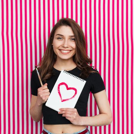Lächelndes Mädchen, das otepad und Pinsel hält Standard-Bild - 82443011