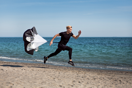 Guy running on beach with parachute