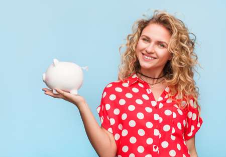 Smiling woman posing with piggy bank