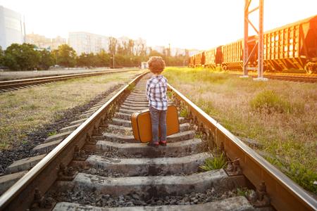 Boy in checkered shirt standing on railways