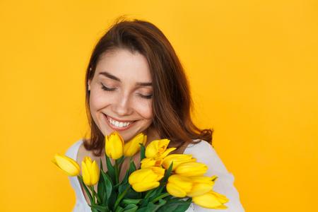 Brunette woman holding flowers smiling