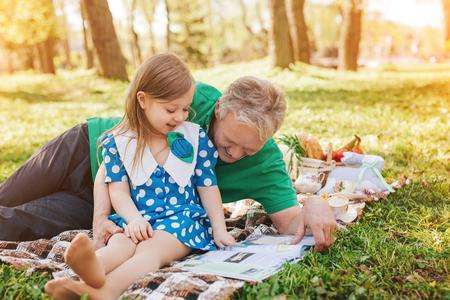 彼の小さな孫娘読書雑誌を抱き締める男