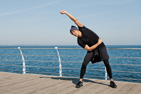 Man warming up in seafront Stock Photo