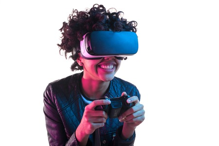 Smiling woman with gamepad wearing VR goggles