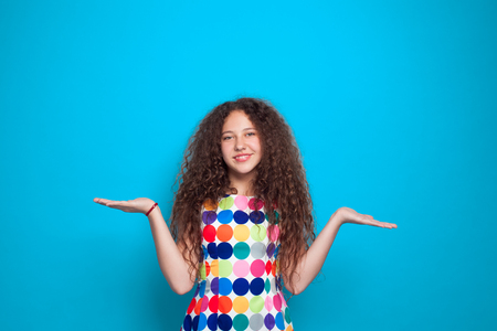 Curly haired girl holding hands palm up