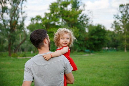 carrying: Father carrying child dressed in red Stock Photo