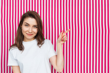 Smiling woman standing against striped background