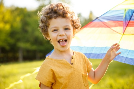 Young boy putting out tongue holding kite