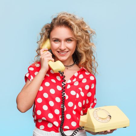 Blonde woman holding old phone with dial Banco de Imagens