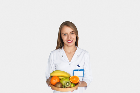 Young girl in whites showing fruits Stock Photo