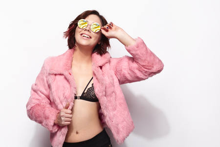 Young model in sunglasses and pink fur
