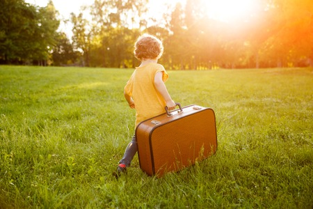 Kid carrying suitcase walking on grass