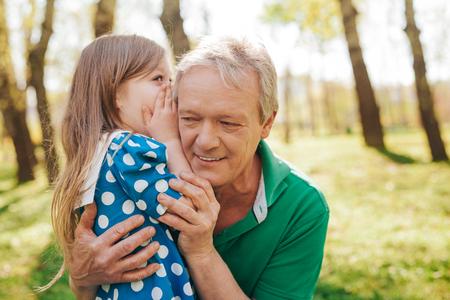 Little girl telling secret to grandpa