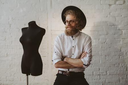 Bearded man wearing hat, shirt, glasses sitting