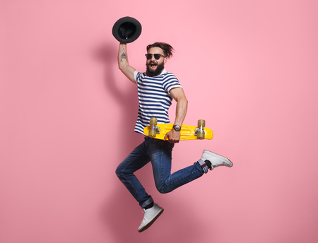 Hipster man jumping with longboard