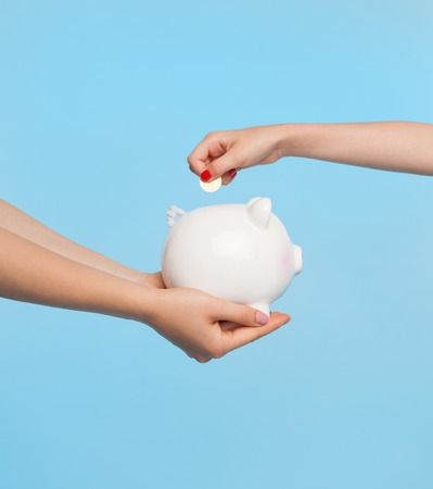 Hands holding piggy bank and coin Stock Photo