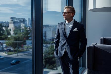 Stijlvolle zakenman poseren in de buurt van venster