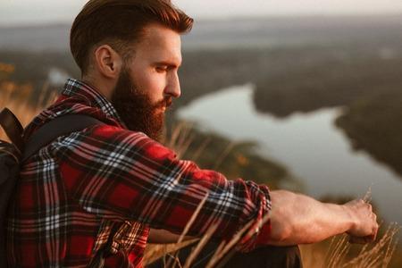 Traveler posing pensively on nature