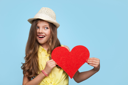 Smiling girl in hat holding heart