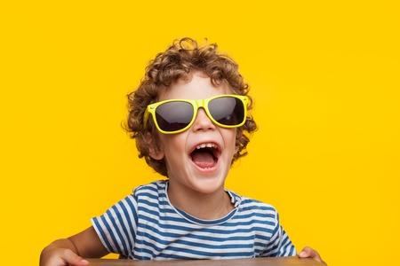 Adorable kid in bright sunglasses on orange