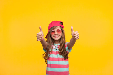 Stylish little girl showing thumbs up